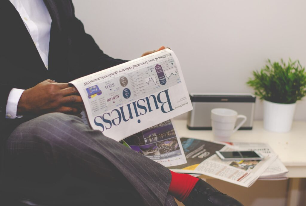 A professional reading a business newspaper