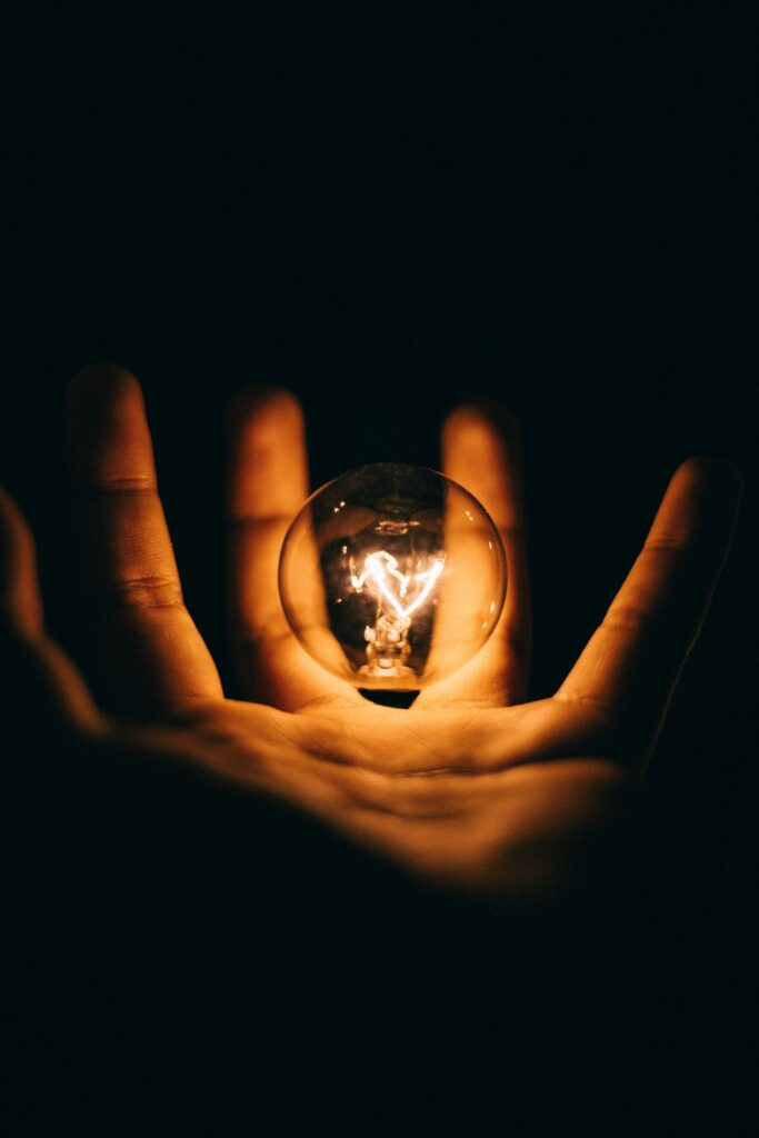 A person holding a lit bulb in the palm