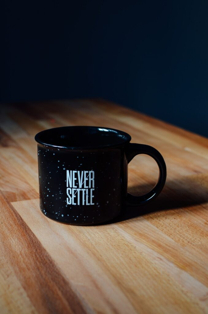 A coffee mug on a wooden table which says 'Never Settle'