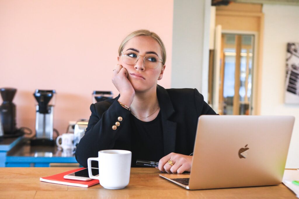 A lady thinking in front of her laptop with a book and coffee mug at the table