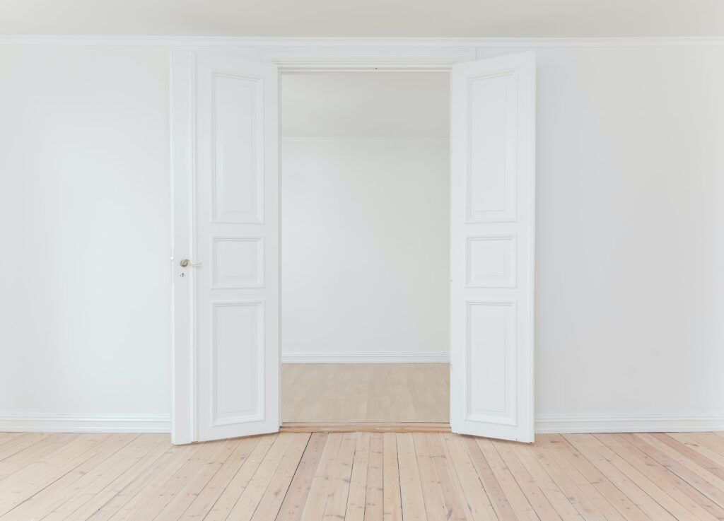 A white door opened to the empty space in the room